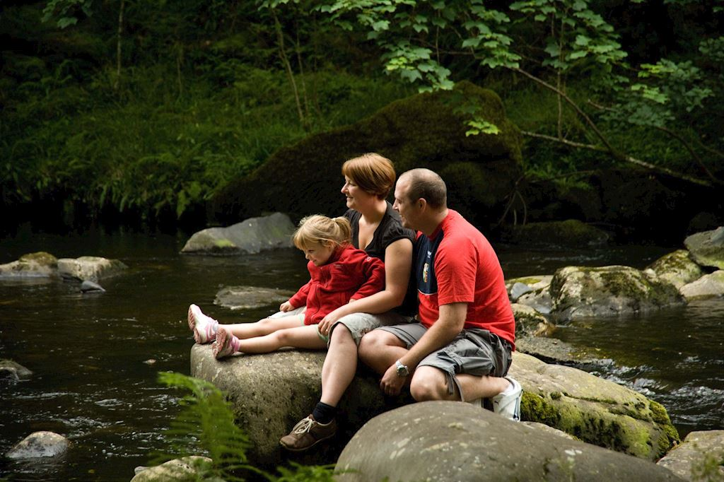 Family group relaxing by the river