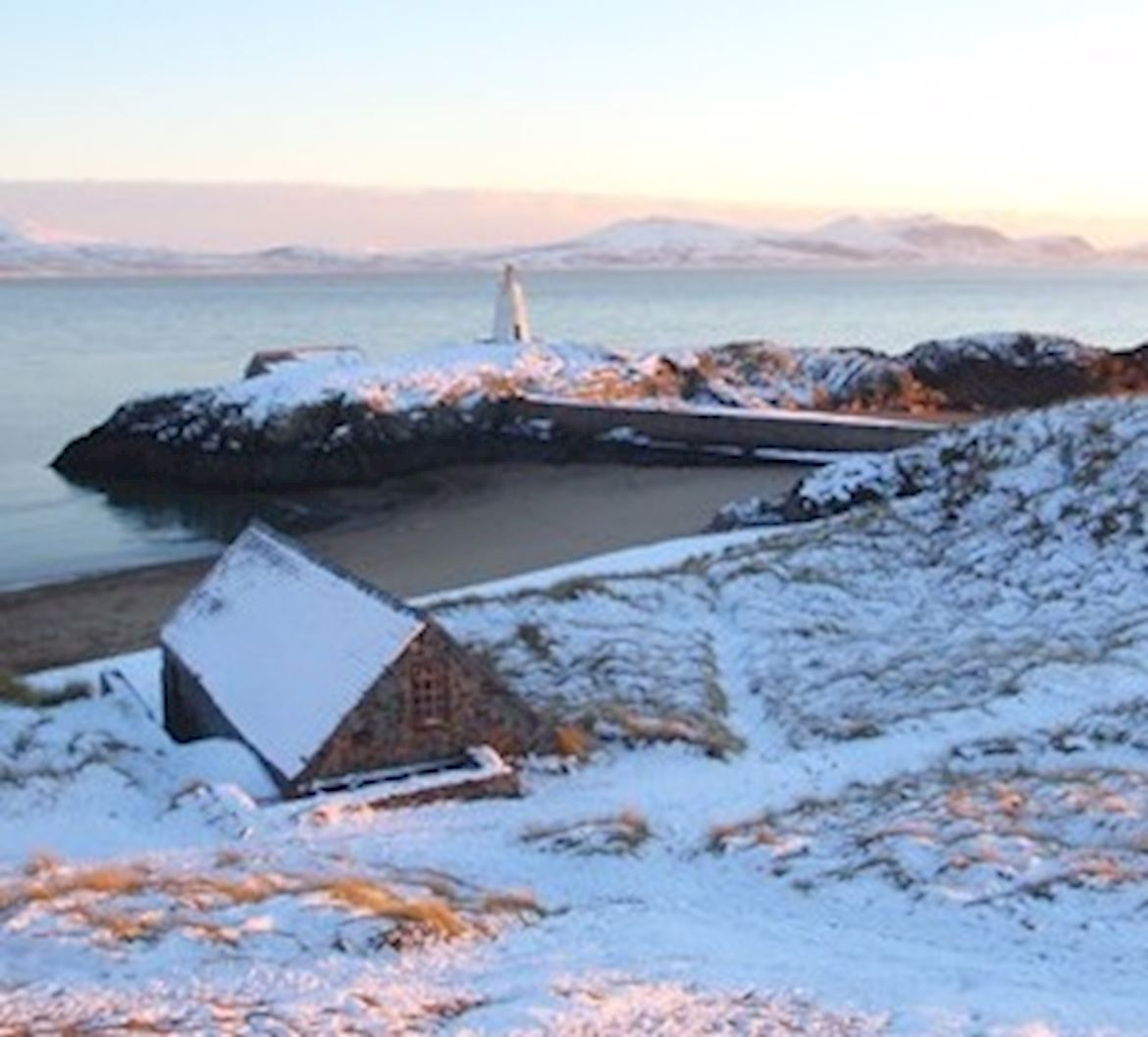 Snow scene in Newborough with snow covered house and cliffs at sunset