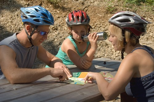 Family sat around a table looking at a trail leaflet