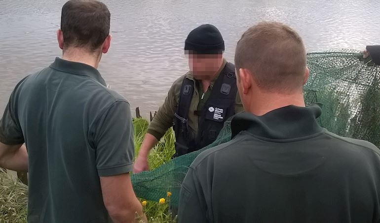 Three men bringing in nets from the river one man who is illegal fishing has his face blanked out