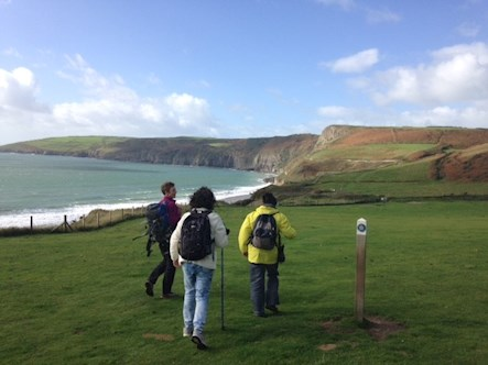 Group of three people walking on the Llyn coastal trail