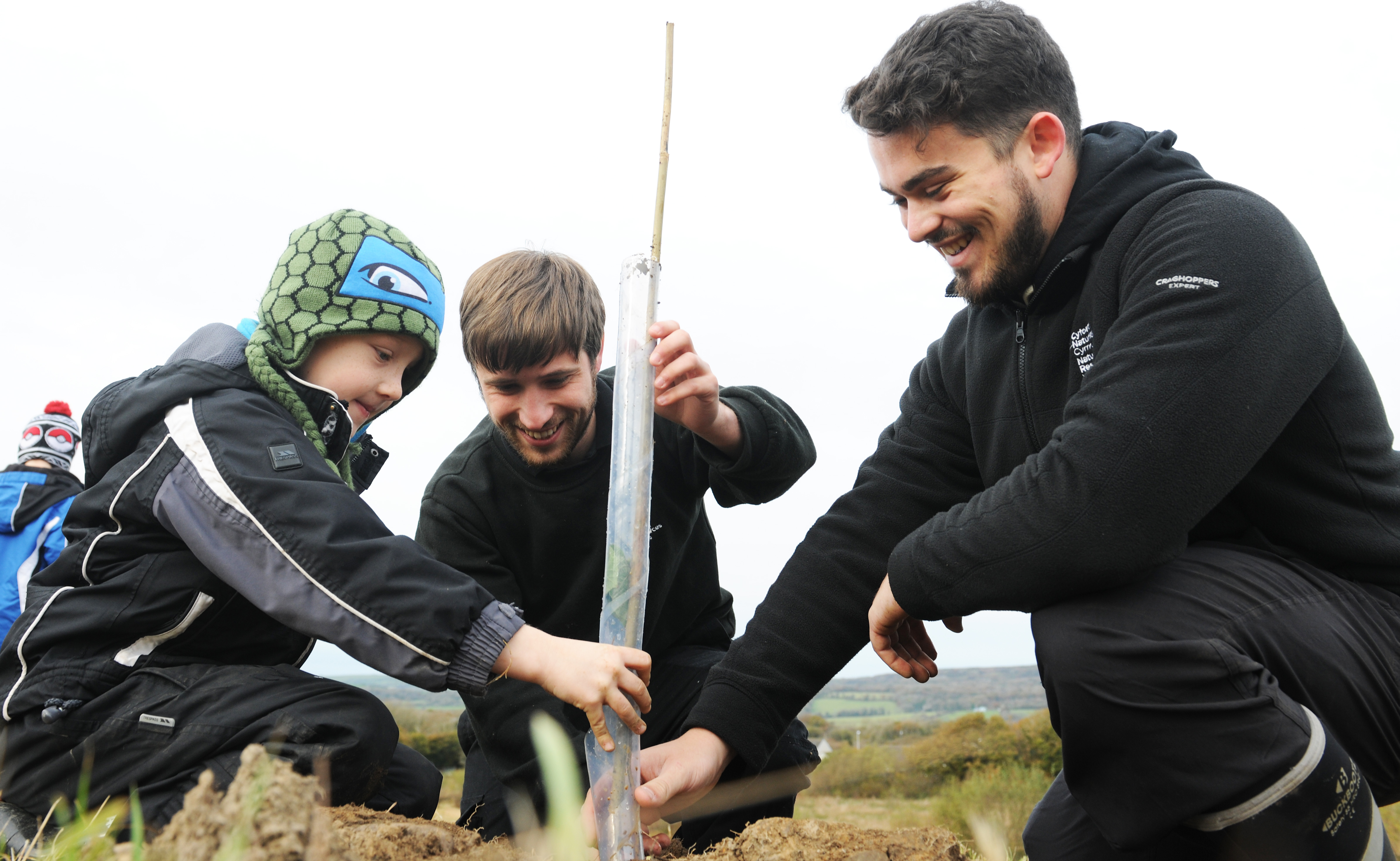 NRW staff with a child planting a tree