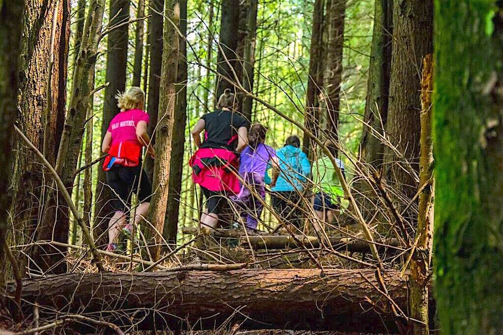 Group of women running through Coed y Brenin Forest