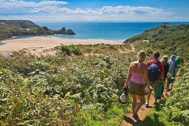 Group of people walking towards the beach at 3 Cliffs Bay Gower