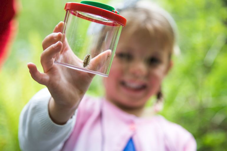 Young girl holding a bug pot