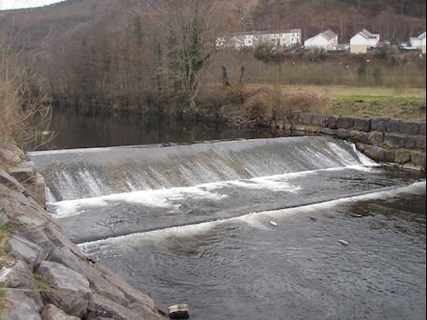 Photo of Merthyr Vale Weir looking upstream of the River Taff with water cascading downstream over the weir